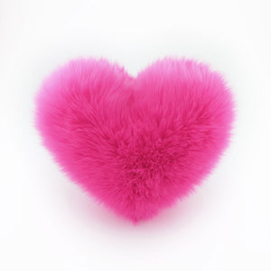 A Hot Pink heart shaped decorative throw pillow.