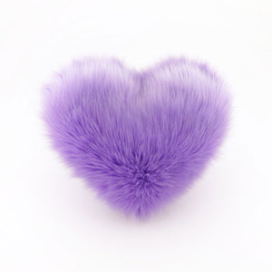 A Lavender faux fur heart shaped decorative pillow.