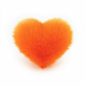 Orange faux fur heart shaped decorative throw pillow.