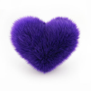 A Purple faux fur heart shaped decorative pillow.