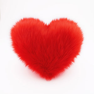 A Scarlet Red faux fur heart shaped decorative pillow.