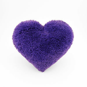 A Purple fluffy shag heart shaped decorative pillow.