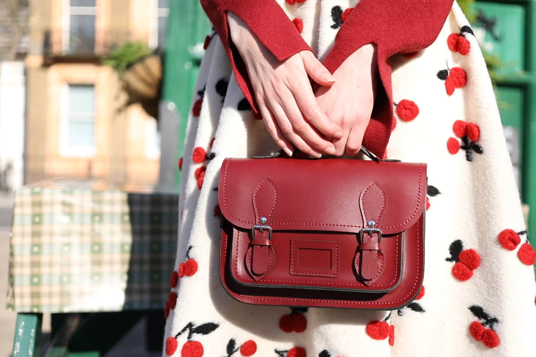 Woman in a dress holding mini satchel handbag in front of herself