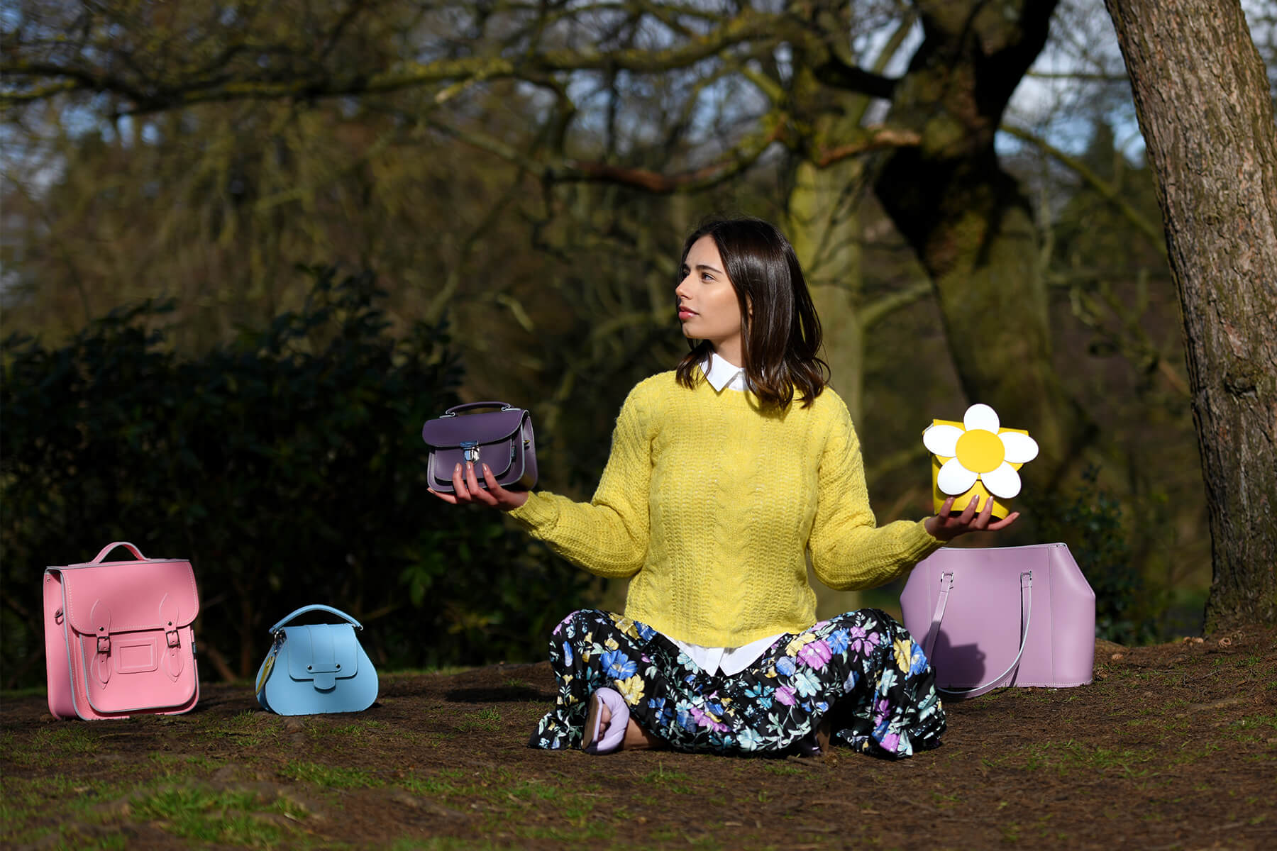 Woman Sat On The Ground Holding bags and surrounded by bags