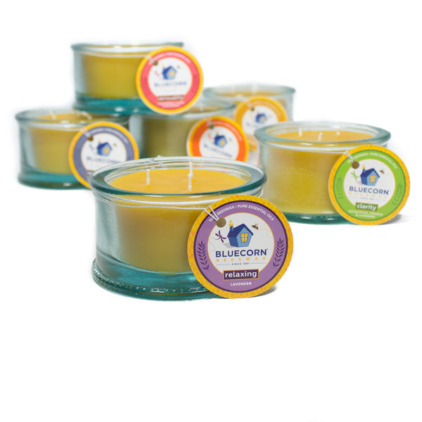 3-wick beeswax candles scented with pure essential oils in all six of Bluecorn's aromatherapy blends. Relaxing, pure lavender, in the foreground, Clarity, Well Being, Sensuality, Uplifting and Tranquility stacked in background.