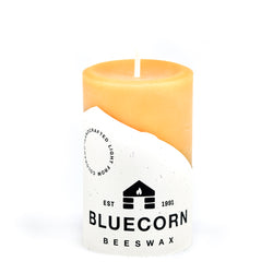 Raw beeswax pillar with Bluecorn Beeswax label. Candle measures 3 inches tall and 2 inches wide, ideally suited for burns of no more than 90 minutes.