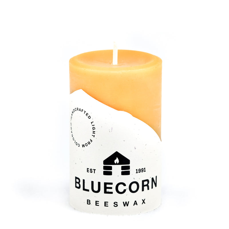 "Raw/ Pure Beeswax Pillar candle from Bluecorn beeswax. Candle measures 3"" tall and 2"" wide and is wrapped in Bluecorn Beeswax label with cabin logo."