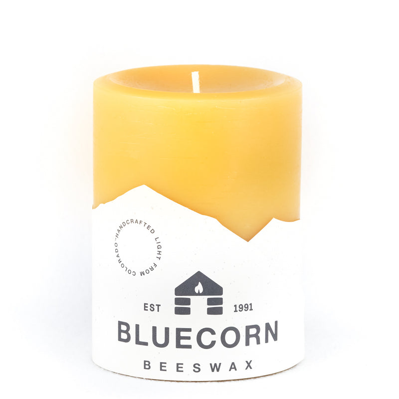 Raw/ Pure Beeswax pillar candle, golden in color, wrapped in blue and white Bluecorn Beeswax label with cabin logo.