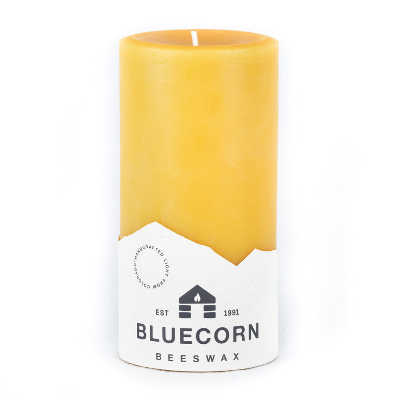Raw/ beeswax pillar from Bluecorn Beeswax. Candle is 4 inches wide and 8 inches tall, best for burns of 6 hours or more at a time. Blue and white label states that the candle is handmade in Colorado of 100% pure beeswax.