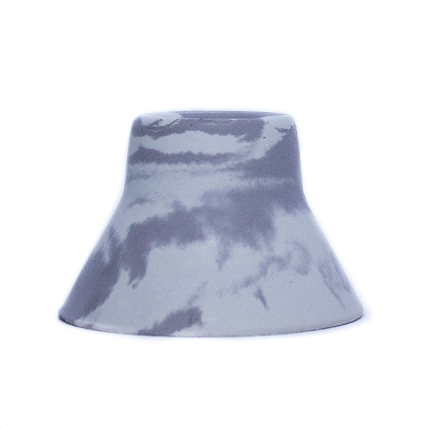 Concrete taper holder in marbled finish, blend of white and charcoal colors. Base is three inches wide and holder tapers, pyramid-like to fit a standard taper candle. Height is 2 inches. Product is handmade so some color and texture variation should be expected.