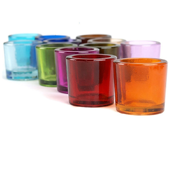Collection of recycled glass holders. Orange and red in the foreground, full array of colors in the background. Holders are about as wide as they are tall with thick-walled glass.