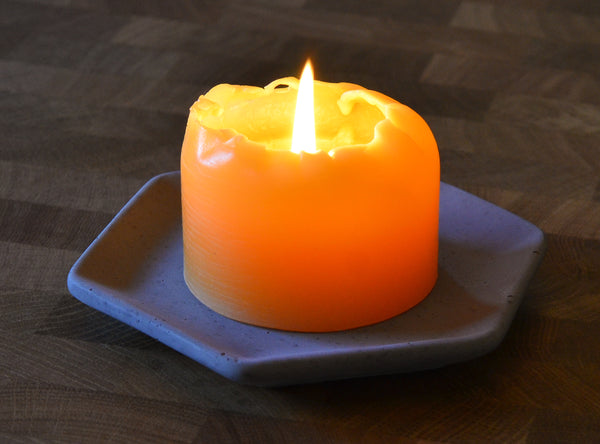 "Image of Bluecorn Beeswax 3"" Pillar candle on concrete hexagon shaped candle base. Beeswax candle is golden yellow in color. Concrete candle base is a warm, dark grey."