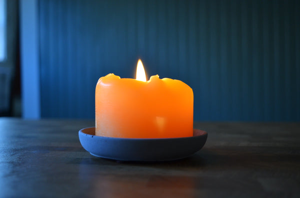 Beeswax candle in a charcoal colored concrete holder. Candle is golden yellow and concrete pillar base is charcoal grey.