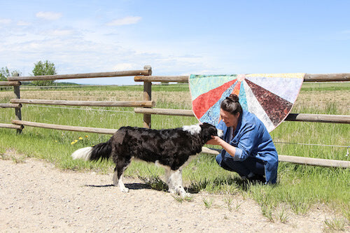 Tannia with a black and white dog on a farm. One of her meditation quilts is on the fence behind her.