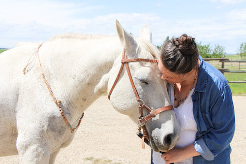"""Tannia with Horse """"Fancy."""" They are embracing each other while wearing matching Sixteen Stones gemstone pieces."""