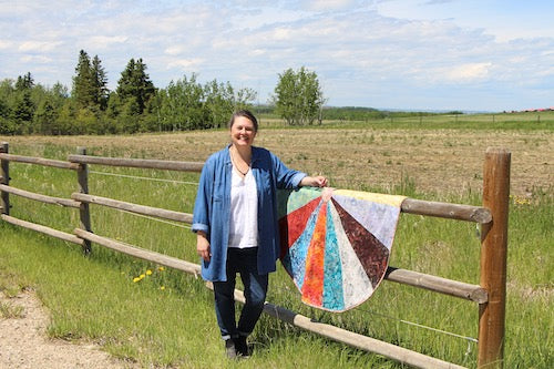 Tannia with quilt on a fence smiling