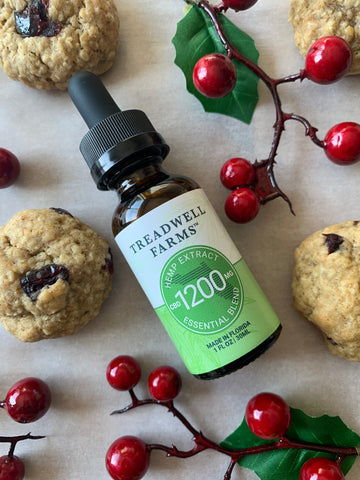 A bottle of Essential Blend CBD Hemp Extract surrounded by holly berries and cookies