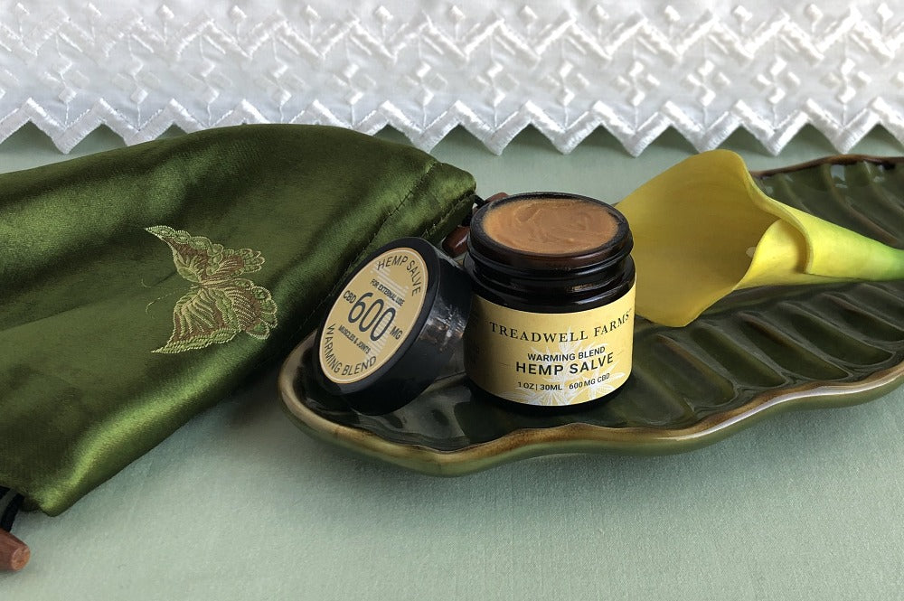A open jar of Treadwell Farms 600 mg CBD Warming Blend Hemp Calve displayed on bedding with a calla lily and silk sash