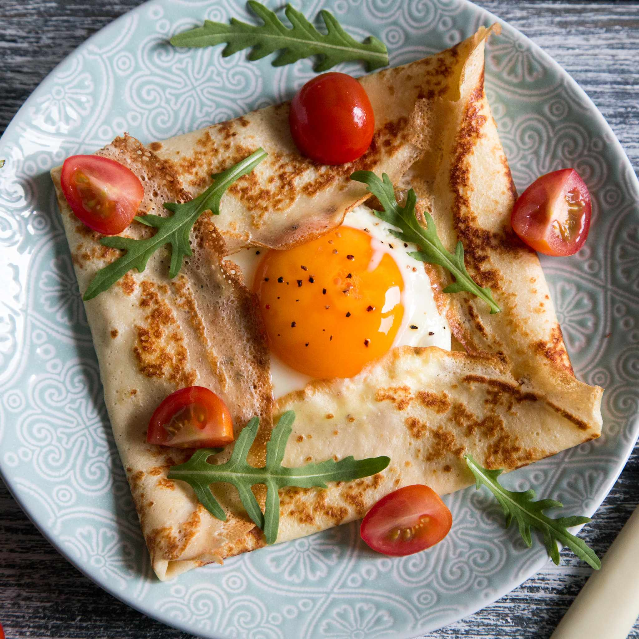 Savoury breakfast crepe filled with egg and scattered with chopped cherry tomatoes and rocket