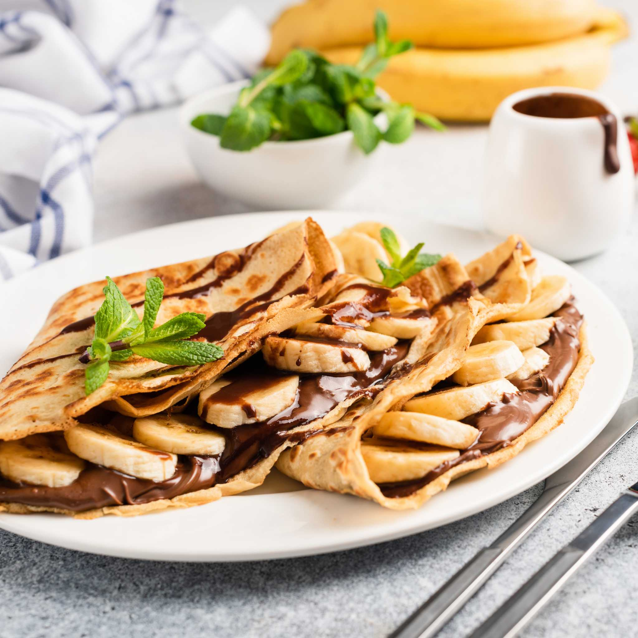 Crepes filled with Nutella and sliced banana and garnished with sprigs of mint
