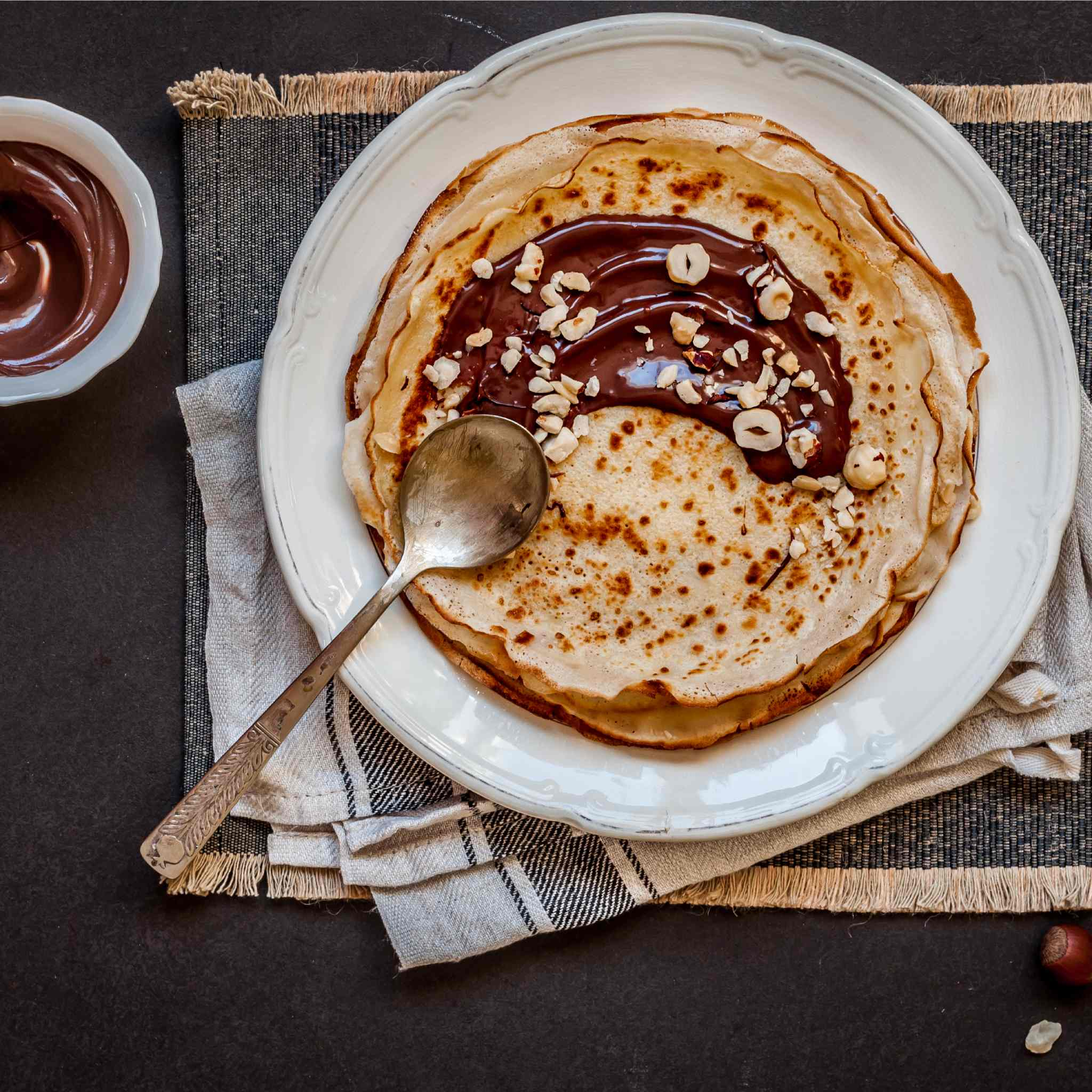 Stack of pancakes spread with Nutella and topped with crushed hazelnuts