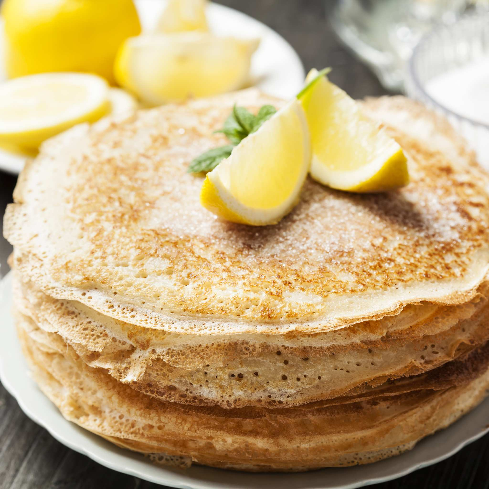 Stack of pancakes sprinkled with sugar and with wedges of lemon on top