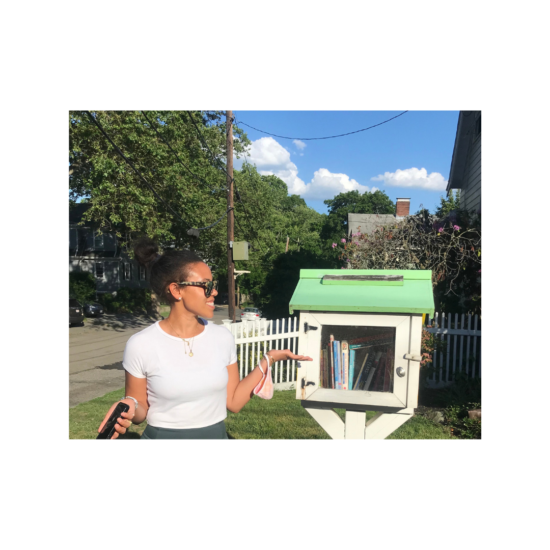Sarah Kayma standing next to the original Free little library which sparked her Little free diverse library project