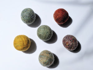 5 wool dryer balls that vary in color from maize, to olive green, to red.