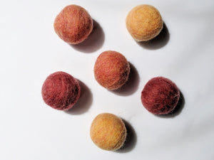 5 wool dryer balls that are warm toned varying from light orange and red to dark orange and red