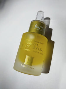 a bottle of facial recovery oil by Eminence. The bottle has a dropper top.