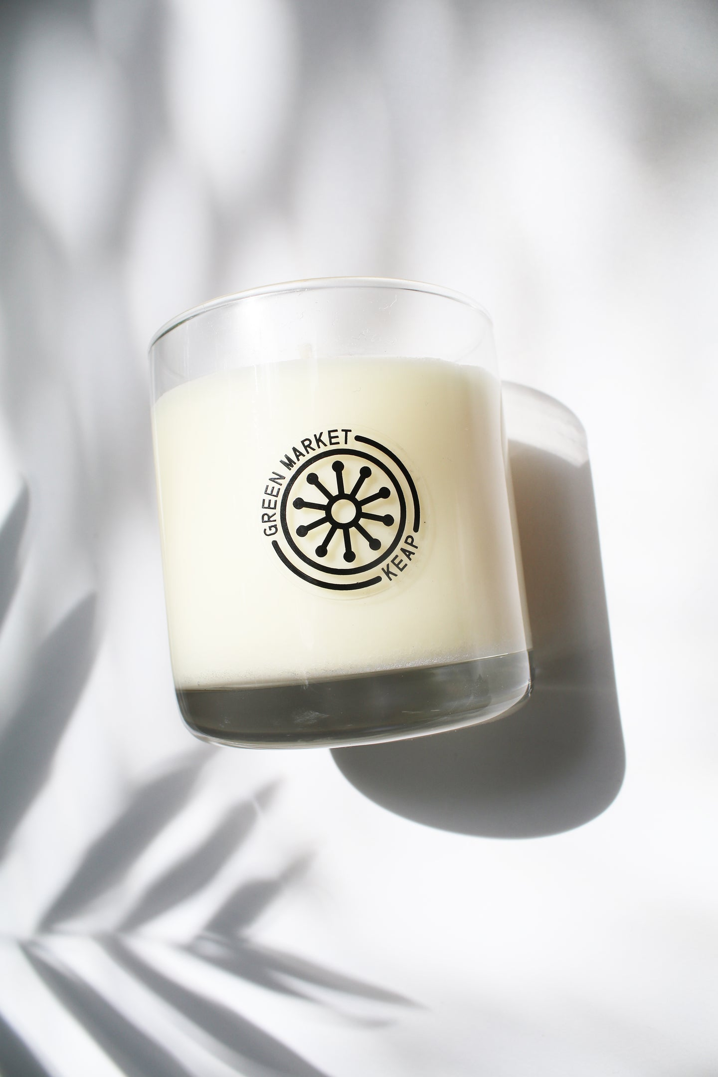 an up close video of a candle - the candle wax is a white color and is inside a clear glass container that doubles as a drinking tumbler once the candle burns out.