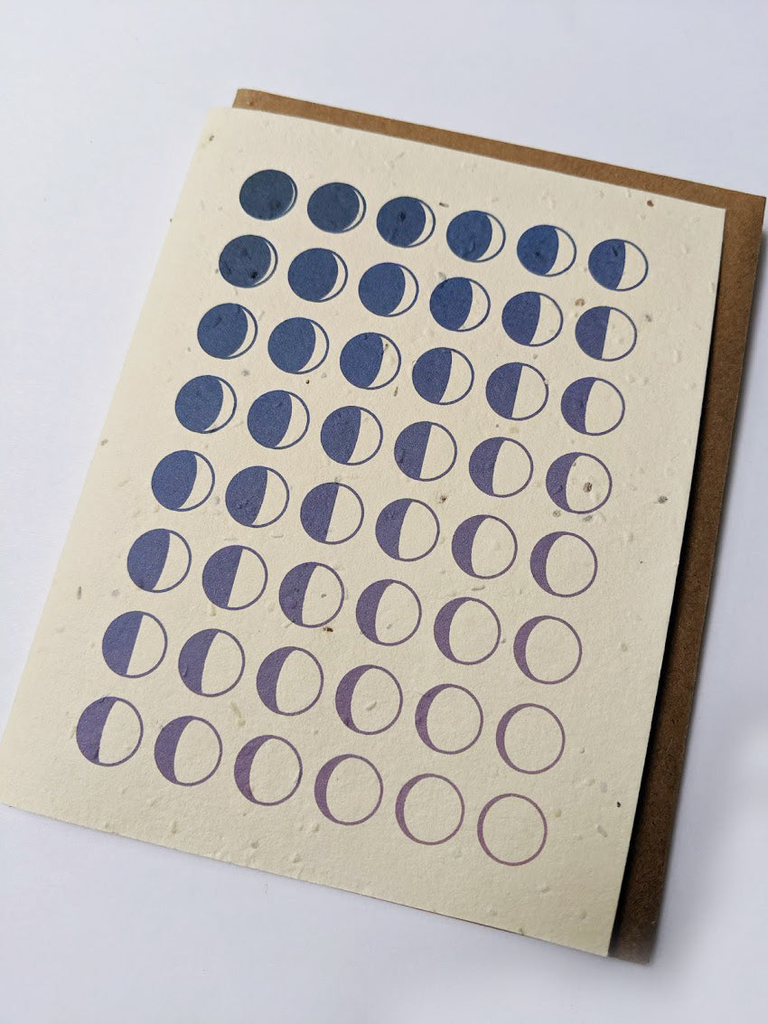 a plantable seed card - the card has a textured look from the seeds imbedded in the paper. There is a drawing of the moon phases on the card in an indigo color