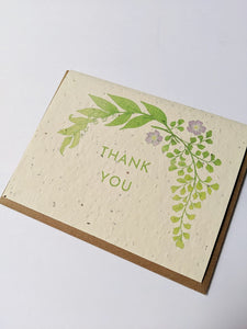 "a plantable seed card - the card has a textured look from the seeds imbedded in the paper. There is a leaf drawing with two small purple flowers on this one that says ""THANK YOU"""