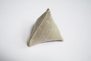 an up close look at a little pyramid made out of hemp. The hemp is a natural light brown color.