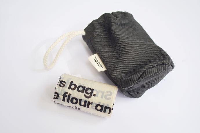 an up close look at a doggie poop bag holder next to the roll of baggies that go inside. The pop bag holder is a gray color. It has a soft cotton handle and a small tag on the side that says