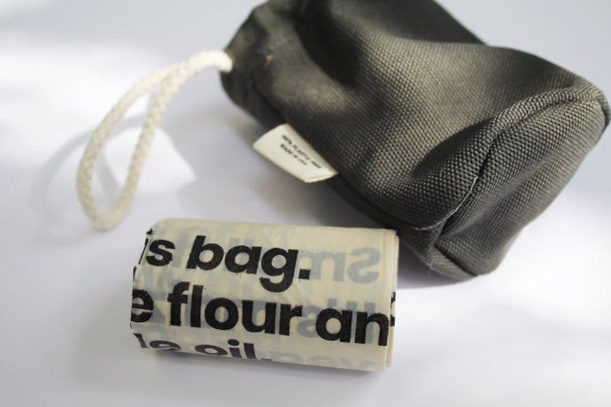 an up close look at the biodegradable poop bags, with the plastic free holder in the background