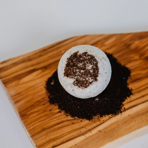 a bath bomb on a wooden table. there are specs of coffee beans in the bath bomb.