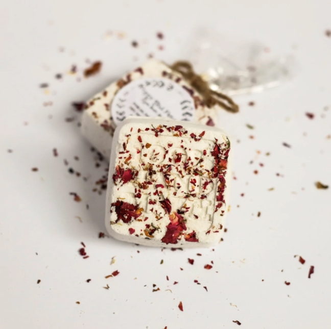 an up close look at a small square bath bomb with rose petals sprinkled on it