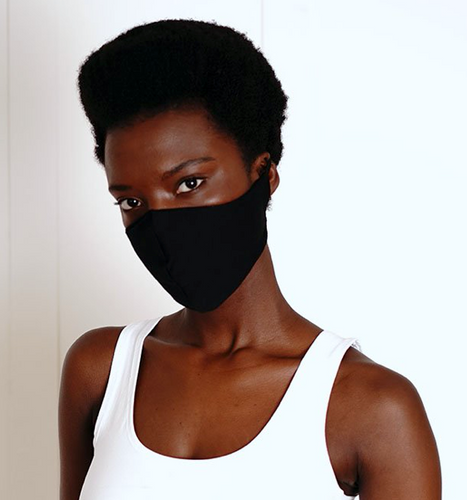 a woman wearing a black organic cotton face mask. The face mask fits snuggly over her nose and sides of her face