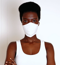 Load image into Gallery viewer, a woman wearing a white organic cotton face mask. The face mask fits snuggly over her nose and sides of her face