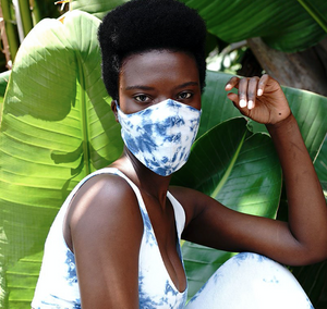 a woman wearing a white and blue tie dye, organic cotton face mask. The face mask fits snuggly over her nose and sides of her face