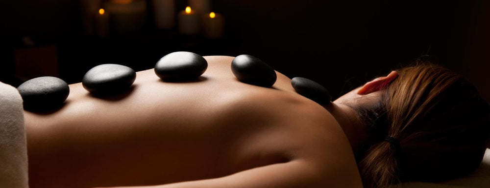 massage with black hot stones on the back