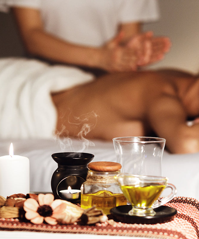 close up banner of focused on oils with aromatherapy massage in the background