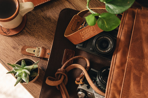 leather camera bag with two cameras and camera straps, a plant and cup of coffee