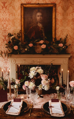 Bridgerton inspired wedding ideas - blush and wine wedding flowers in front of classically decorated fireplace