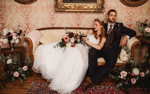 Autumnal wedding inspiration image showing bride and groom with blush and burgundy flowers
