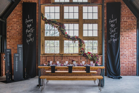 Modern Gothic Romance Wedding Tablescape with Black Wal Hangings against exposed brick walls and picture window.
