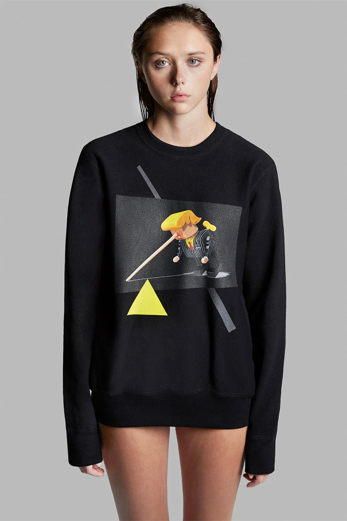 A black, satirical, high-end anti-Trump sweatshirt. Printed on the sweatshirt is an image of Trump as an antique toy villain is tipping over due to his long Pinocchio nose's weight. There are grey and yellow graphics printed on the sweatshirt complementing the unusually shaped image. The design is inspired by the work of the artist Malevich.