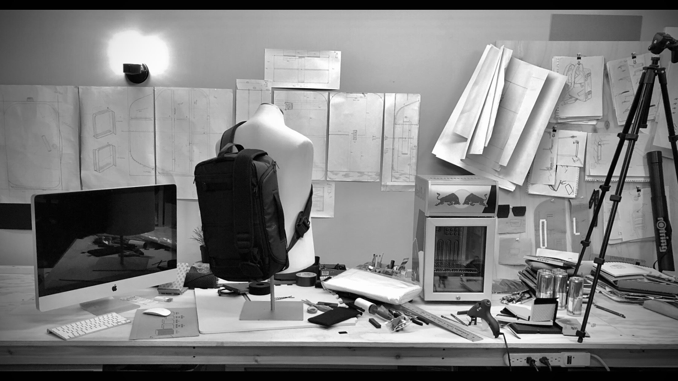 inside office space with camera bag designs, prototype, desktop computer and camera tripod on desk