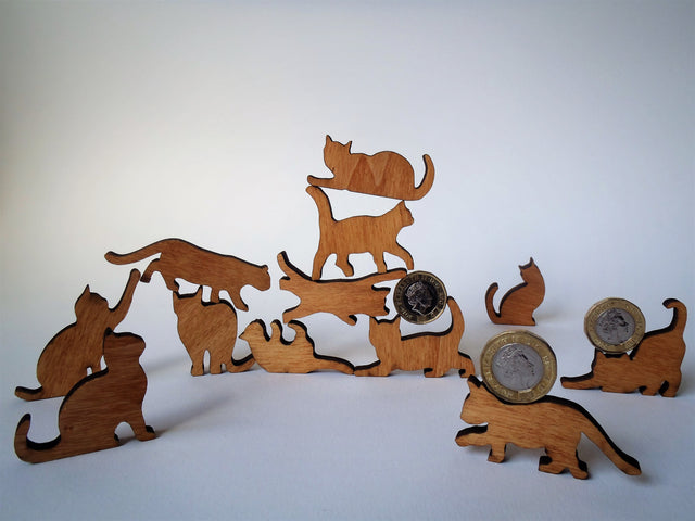 twelve wooden cat ornaments in a pile